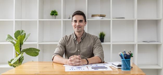 Portrait d'un bel homme assis au bureau. une nouvelle génération d'hommes d'affaires a fondé une start-up et a réussi à développer son entreprise rapidement. concept de portrait d'entreprise.