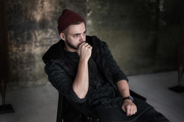 Portrait d'un bel homme assis confortablement dans un loft tendance