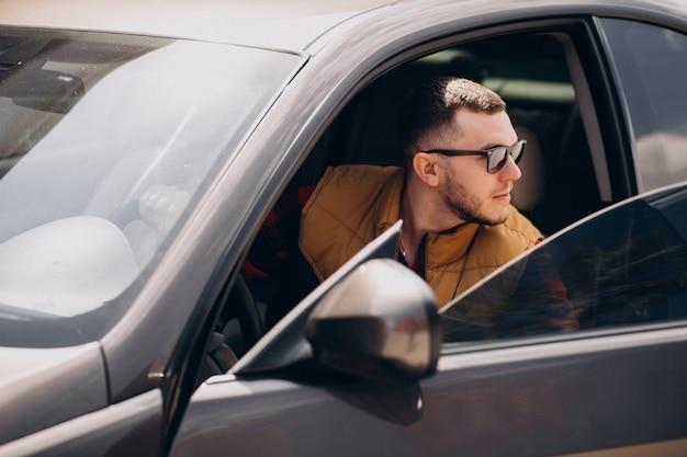 Portrait de bel homme assis dans la voiture