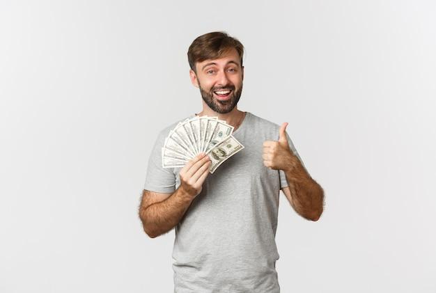Portrait de bel homme avec barbe, montrant le pouce vers le haut et tenant de l'argent
