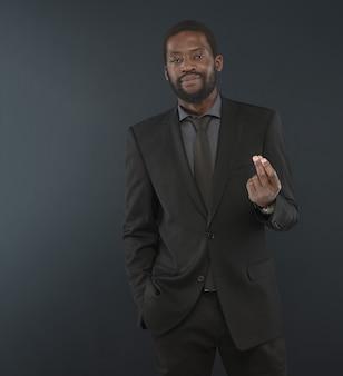 Portrait de bel homme barbu d'âge moyen. afro homme vêtu d'une chemise de couleur charbon, suif noir avec cravate pose
