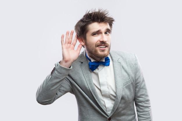 Portrait d'un bel homme barbu attentif en costume gris décontracté et noeud papillon bleu debout tenant la main près de l'oreille et essayant d'entendre. tourné en studio intérieur, isolé sur fond gris clair.