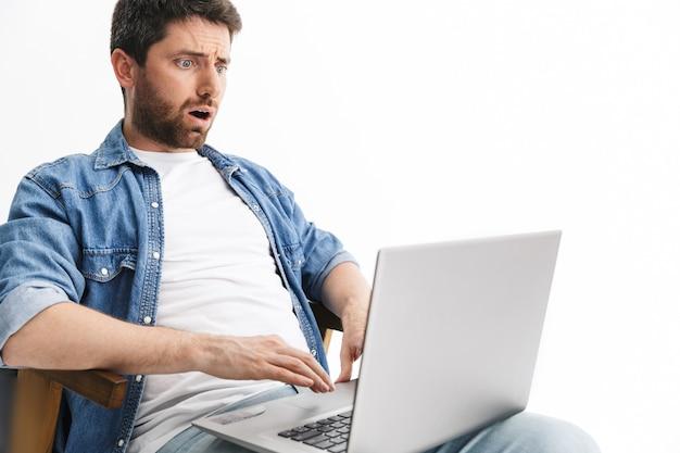 Portrait d'un bel homme barbu choqué portant des vêtements décontractés assis sur une chaise isolée sur un mur blanc, travaillant sur un ordinateur portable