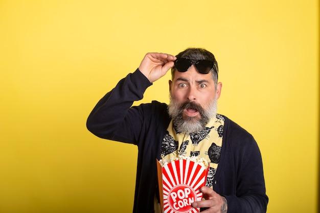 Portrait de bel homme barbu effrayant attrayant, soulevant des lunettes de soleil avec une chemise jaune et une veste bleue, manger du pop-corn en regardant une vidéo effrayante isolée sur fond jaune.