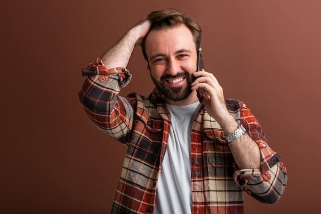 Portrait de bel homme barbu élégant sur brun