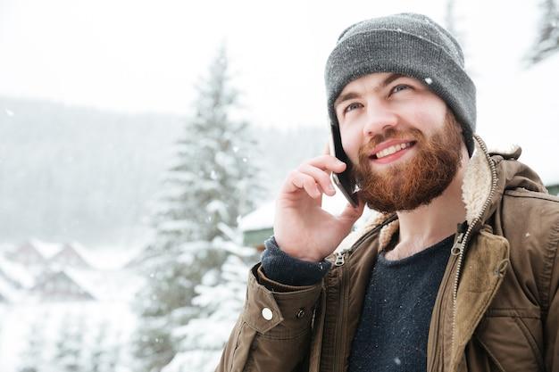 Portrait d'un bel homme barbu gai samiling et parlant au téléphone portable à l'extérieur en hiver