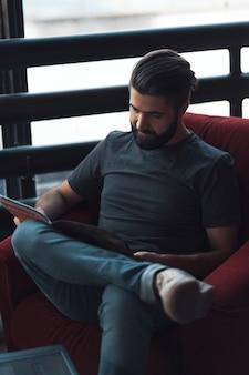 Portrait bel homme barbu portant des vêtements décontractés, assis dans une chaise rouge loft moderne