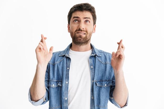 Portrait d'un bel homme barbu portant des vêtements décontractés debout isolé, tenant les doigts croisés pour la bonne chance