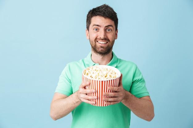 Portrait d'un bel homme barbu portant des vêtements décontractés, isolé sur un mur bleu, mangeant du pop-corn en regardant un film