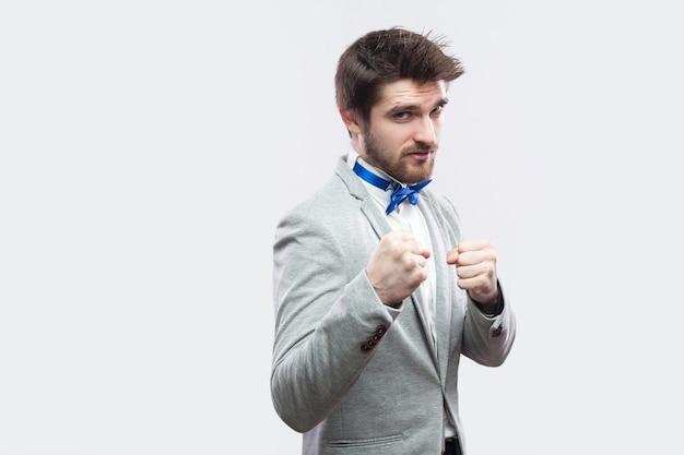 Portrait d'un bel homme barbu sérieux en costume gris décontracté et noeud papillon bleu debout et regardant la caméra avec des poings de boxe et prêt à attaquer. tourné en studio, isolé sur fond gris clair.