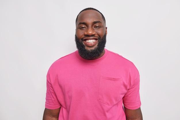 Portrait d'un bel homme barbu sourit joyeusement à l'avant, montre des dents blanches parfaites, de bonne humeur, se sent satisfait, vêtu d'un t-shirt rose de base, pose à l'intérieur