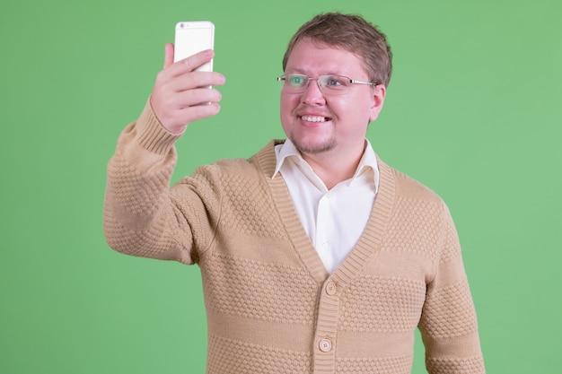 Portrait de bel homme barbu en surpoids avec des lunettes contre clé chroma ou mur vert