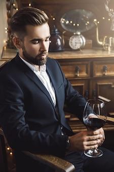 Portrait de bel homme barbu avec un verre de vin rouge
