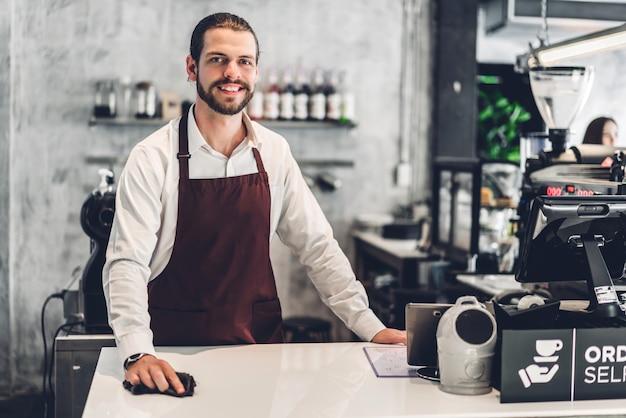 Portrait de bel homme barista barbu propriétaire de petite entreprise travaillant derrière le comptoir bar dans un café