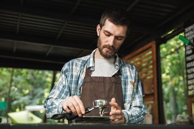 Portrait d'un bel homme barista portant un tablier faisant du café tout en travaillant dans un café de rue ou un café en plein air