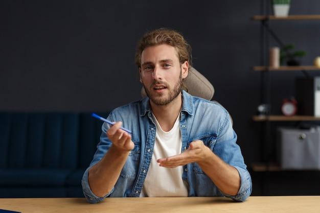 Portrait d'un bel homme bouclé aux cheveux longs souriant utilisant un ordinateur portable pour une réunion en ligne en appel vidéo. travail à domicile. communication en ligne avec des collègues et des indépendants et vidéoconférence.
