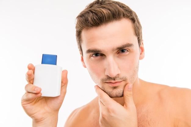 Portrait de bel homme avec une bouteille de lotion à la main