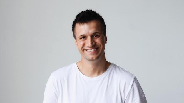 Portrait d'un bel homme caucasien heureux, souriant amicalement en regardant la caméra