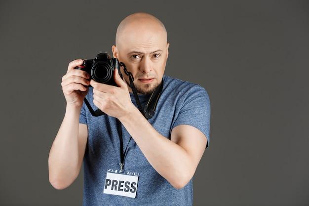 Portrait de bel homme en chemise grise avec photocamera et badge presse prendre des photos sur un mur sombre