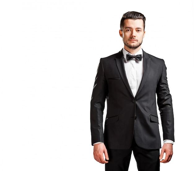 Portrait de bel homme confiant en costume noir avec noeud papillon