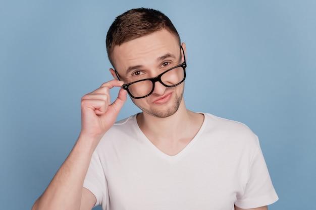 Portrait d'un bel homme confiant et intelligent touchant ses lunettes isolées sur fond de couleur bleu