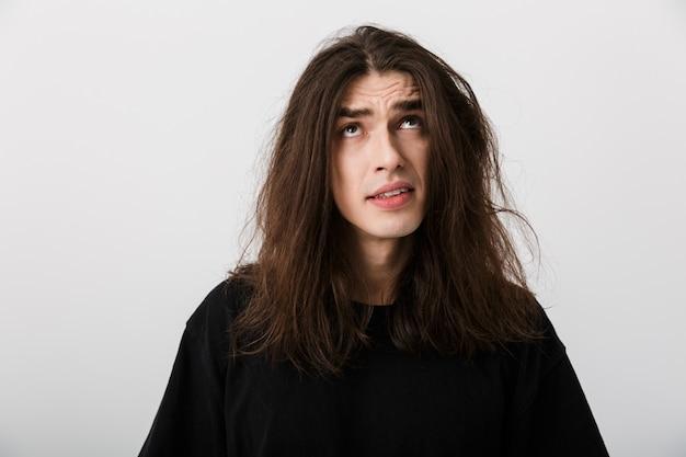 Portrait d'un bel homme confus aux cheveux longs en équilibre et regardant vers le haut sur fond blanc