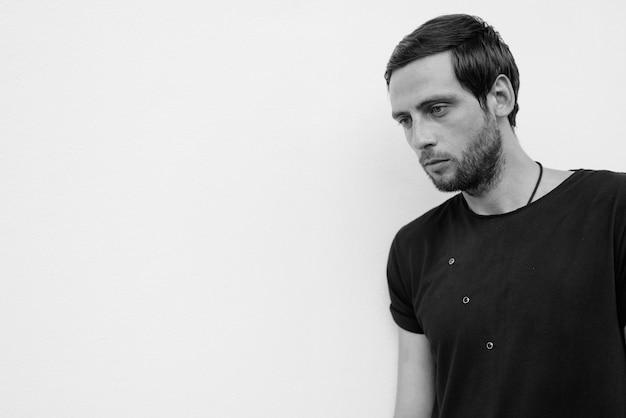 Portrait d'un bel homme contre un mur blanc à l'extérieur en noir et blanc