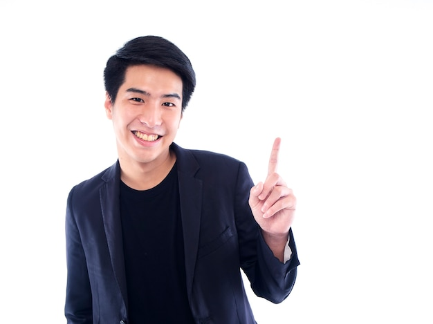 Portrait de bel homme émotionnel pointant sur un mur blanc. espace pour le texte