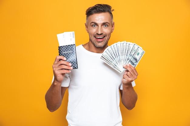 Portrait d'un bel homme émotionnel posant isolé sur un mur jaune tenant un passeport avec des billets et de l'argent.