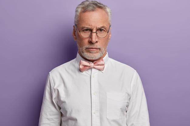 Portrait de bel homme européen aux cheveux gris regarde avec une expression de visage stricte à travers des lunettes rondes, porte une chemise blanche formelle et noeud papillon