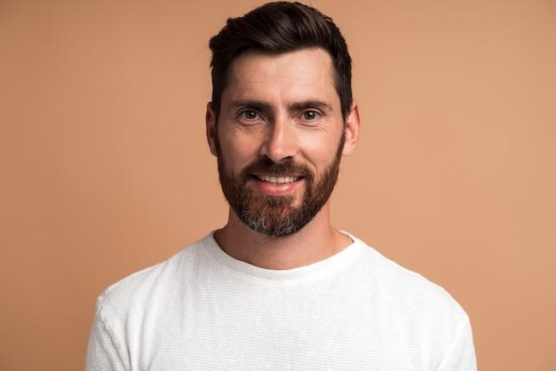 Portrait d'un bel homme gai en chemise blanche regardant la caméra, se sentant joyeusement comme s'il avait une idée intéressante. studio shot isolé sur fond beige