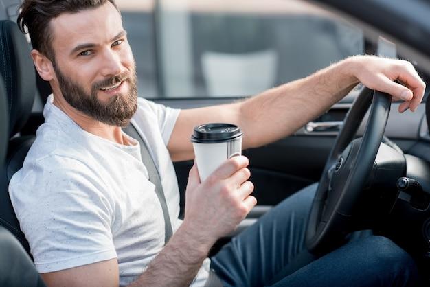 Portrait d'un bel homme habillé en t-shirt blanc décontracté au volant d'une voiture avec du café à emporter