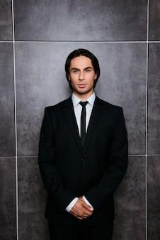 Portrait de bel homme hispanique confiant debout près de mur gris