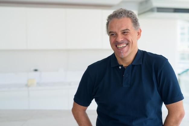 Portrait de bel homme hispanique mature dans la maison contemporaine moderne à l'intérieur