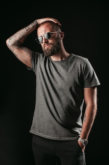 Portrait d'un bel homme avec une longue barbe bien garnie, lunettes de soleil et une chemise grise