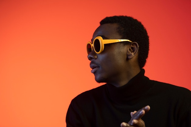 Portrait de bel homme avec des lunettes de soleil sur fond orange