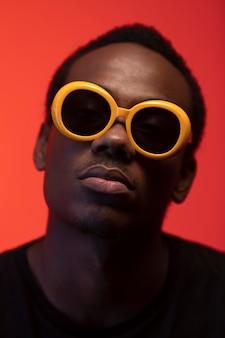 Portrait De Bel Homme Avec Des Lunettes De Soleil Sur Fond Orange Photo gratuit