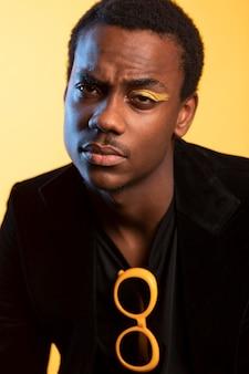 Portrait d'un bel homme avec des lunettes de soleil et maquillage des yeux sur fond jaune