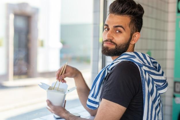 Portrait d'un bel homme mangeant des nouilles chinoises dans un café et regardant par la fenêtre. le concept de la cuisine asiatique saine.