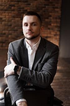Portrait bel homme à la mode dans une chemise blanche est assis sur une chaise dans un studio photo loft