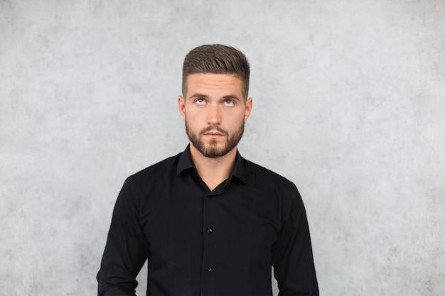 Portrait d'un bel homme à la mode heureux en chemise noire regardant la caméra.