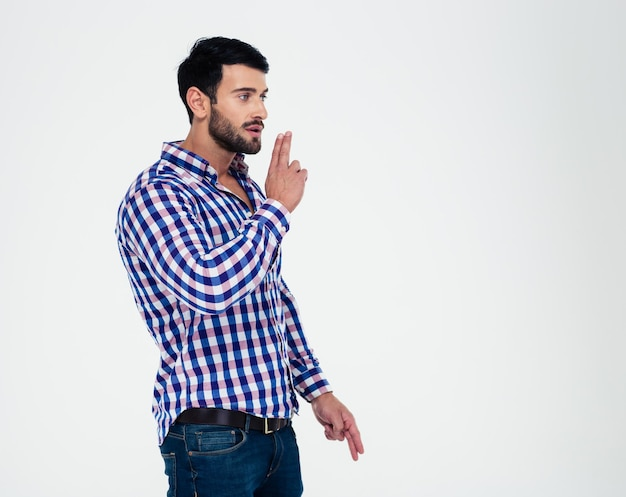 Portrait d'un bel homme montrant le geste des armes à feu avec les doigts isolés sur un motif blanc