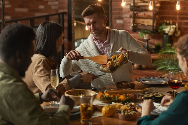 Portrait de bel homme mûr servant de la nourriture tout en accueillant un dîner avec des amis et la famille,