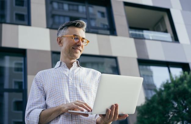 Portrait de bel homme mûr souriant à l'aide d'un ordinateur portable, communication, saisie, travail en ligne