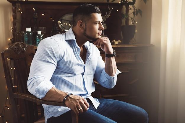 Portrait de bel homme musclé vêtu d'une chemise bleue