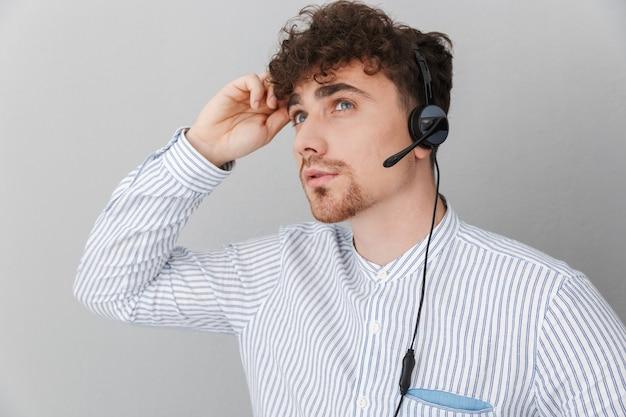 Portrait d'un bel homme opérateur téléphonique réfléchi portant un casque de microphone travaillant au bureau et parlant avec un client isolé sur un mur gris