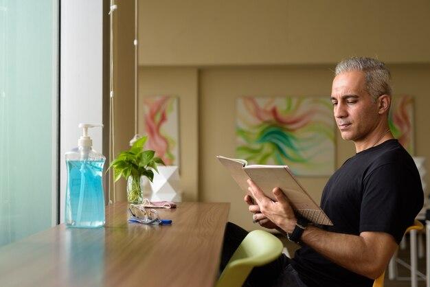 Portrait de bel homme persan aux cheveux gris à la bibliothèque à l'intérieur d'un bâtiment moderne