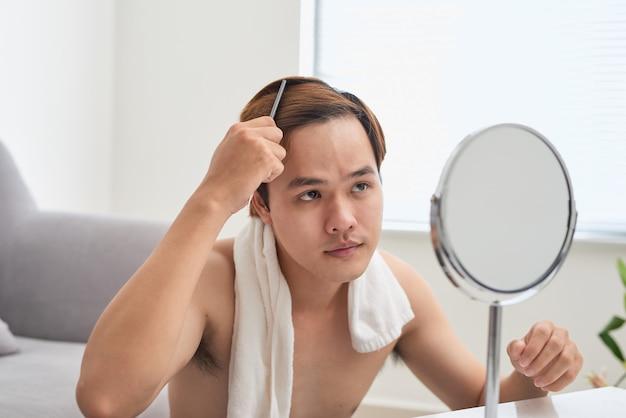 Portrait d'un bel homme se regardant dans le miroir et se brossant les cheveux.