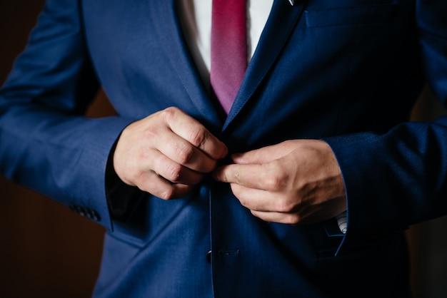 Portrait de bel homme sérieux en costume bleu et cravate boutonnage veste