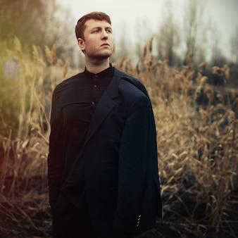 Portrait bel homme sérieux en manteau à l'extérieur dans le parc automne